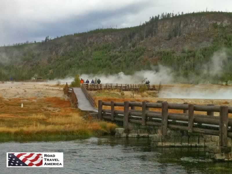 Visitors walk a wooden bridge across a geothermal area at Yellowstone National Park